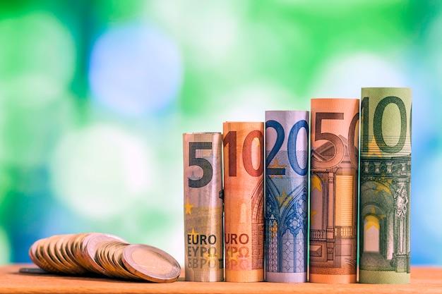 Cinq, dix, vingt, cinquante et cent euros des billets de banque, avec des pièces en euros sur fond de bokeh flou vert.