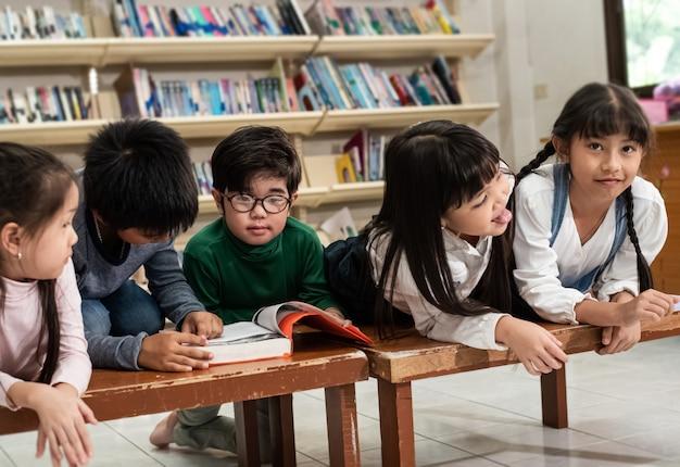 Cinq enfants allongés sur un bureau en bois, parler et lire un livre, faire de l'activité ensemble, à l'école, une lumière floue autour