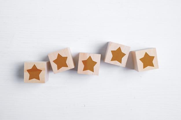 Cinq étoiles sur des blocs de bois affichant la meilleure note. meilleur score. mise à plat.