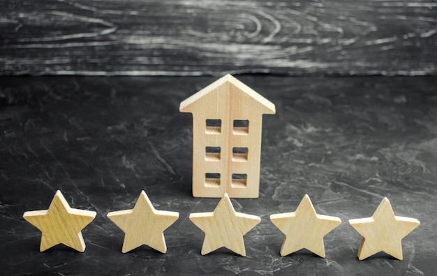 Cinq étoiles et une maison en bois sur un fond de béton gris.