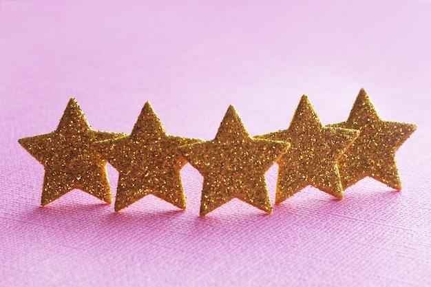 Cinq étoiles d'or sur fond rose.