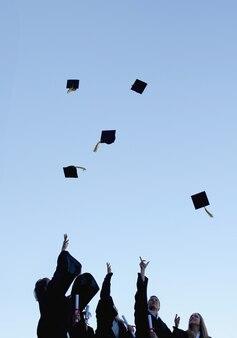 Cinq étudiants diplômés jetant leurs chapeaux haut dans le ciel