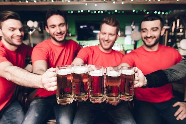Cinq fans de sport buvant de la bière au bar.