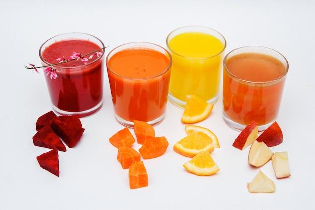 Cinq grands verres avec jus de carotte, concombre, tomate, betterave et citrouille, légumes isolés sur fond blanc.