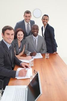 Cinq hommes d'affaires lors d'une réunion en souriant à la caméra