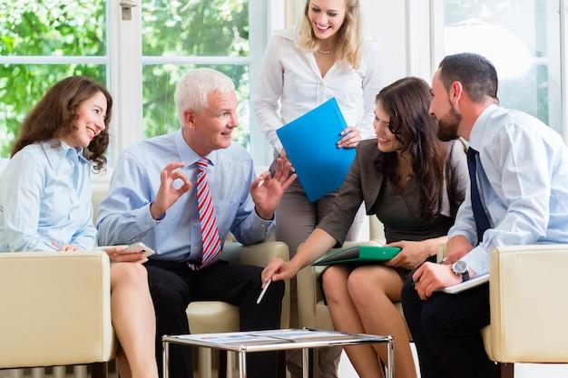 Cinq hommes d'affaires en réunion d'équipe étudient des graphiques