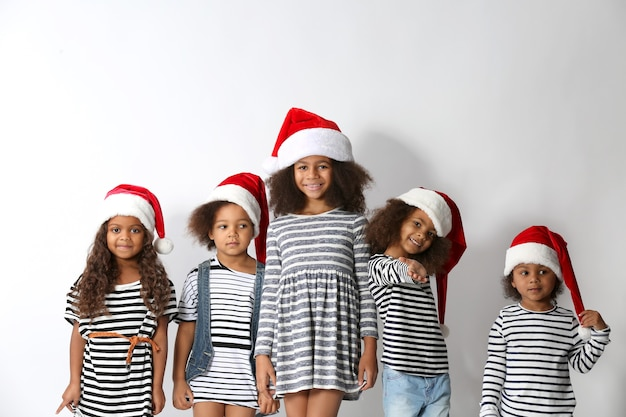 Cinq jolies filles africaines en vêtements rayés et chapeaux de noël sur fond blanc