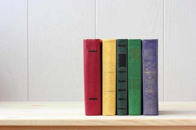 Cinq livres aux couvertures dures colorées sur la table.