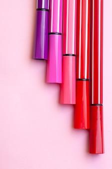 Cinq marqueurs ou stylos de couleur rose, violet, rose se trouvent comme des marches sur un rose