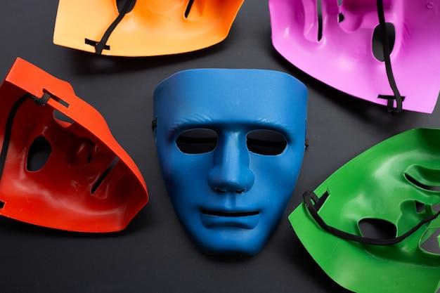 Cinq masques faciaux sur une surface sombre.