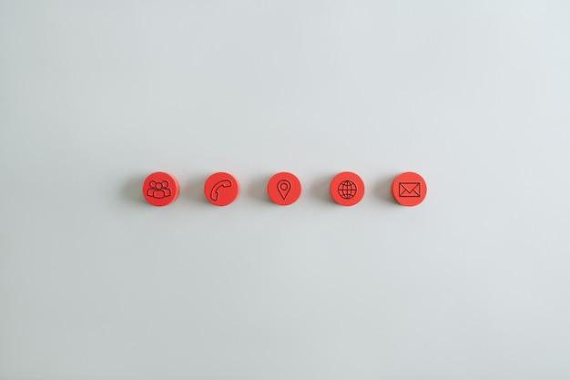 Cinq morceaux de bois ronds rouges dans une rangée avec des icônes de contact et d'information sur eux.