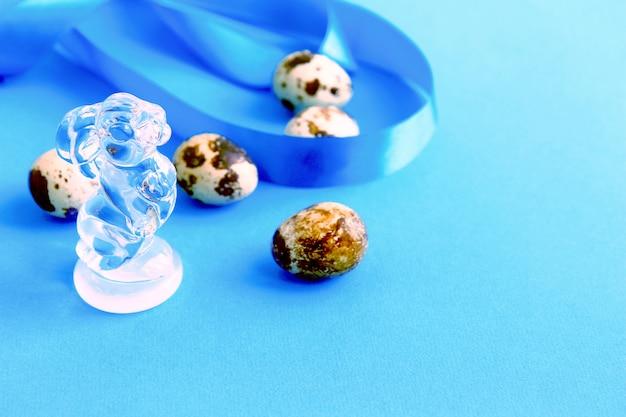 Cinq œufs de caille mouchetés, ruban de satin bleu et figurine de lapin en verre transparent fond bleu concept vue de dessus de pâques
