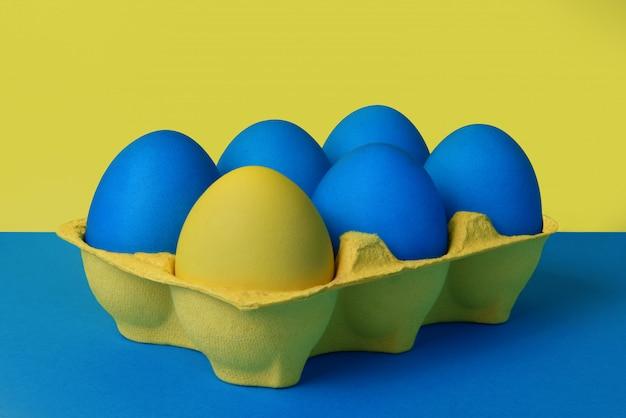 Cinq oeufs de pâques peints en bleu et un en jaune dans un emballage jaune sur fond bleu et jaune