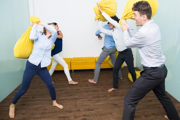 Cinq personnes excitées se battent avec des oreillers