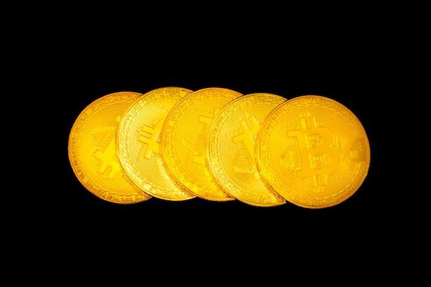 Cinq pièces bitcoin sur fond noir