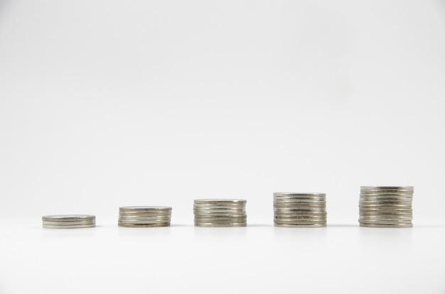 Cinq piles de pièces thaïlandaises sur fond blanc
