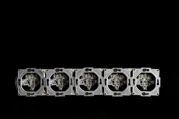 Cinq sorties en ligne, démontées et montées dans un mur de verre noir