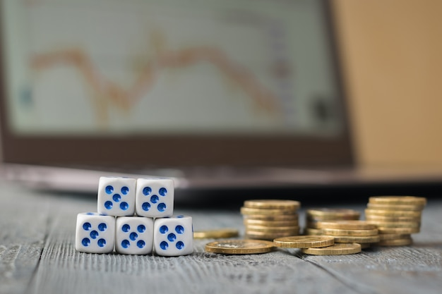 Cinq dés et un tas de pièces de monnaie devant un ordinateur portable avec des horaires d'affaires.