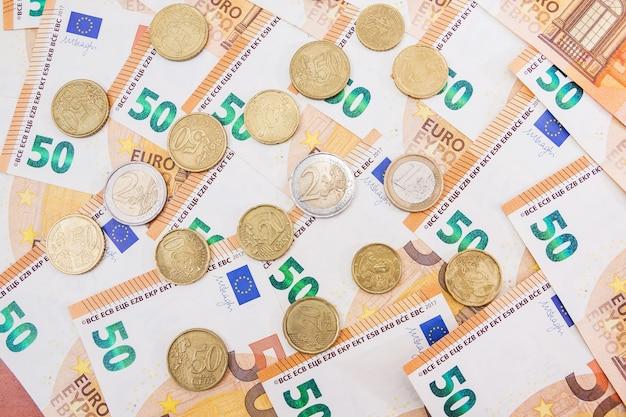 Cinquante billets et pièces en euros. fond d'argent.