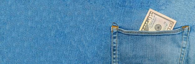 Cinquante dollars dans la poche arrière d'un jean bleu. concept de richesse et de prospérité.