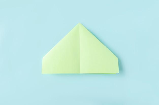 Cinquième étape de la fabrication d'un papillon en papier origami avec du papier vert, des ciseaux sur fond bleu