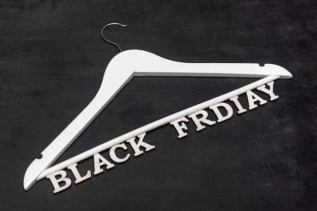 Cintre blanc et inscription black friday. offre spéciale. fond noir. réductions. vente saisonnière.