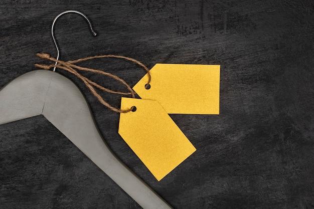 Cintre en bois avec étiquettes en papier jaune, fond noir. maquette d'étiquette vierge. étiquette de vêtements.