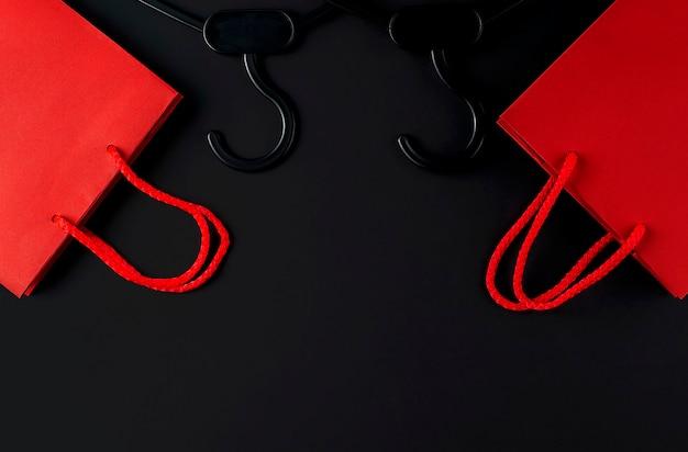 Cintre noir et sac rouge sur fond noir. concept de vente de vendredi noir. espace de copie