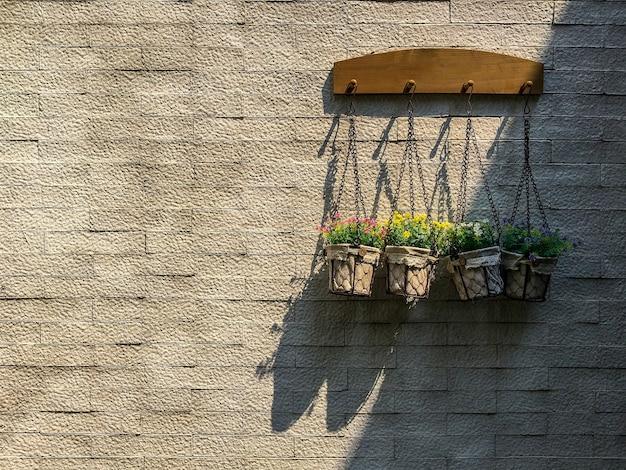 Cintre de pots de fleurs avec barre de suspension en bois sur fond de mur de brique dans la lumière du soleil et l'ombre