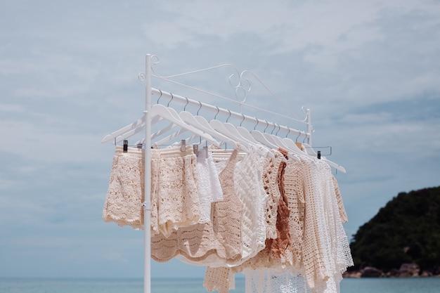 Cintre de sol avec des vêtements tricotés élégants sur la plage tropicale