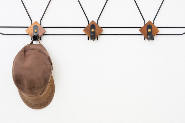 Cintre vide avec des éléments en métal noir et en bois sur un mur et une casquette texturés blancs