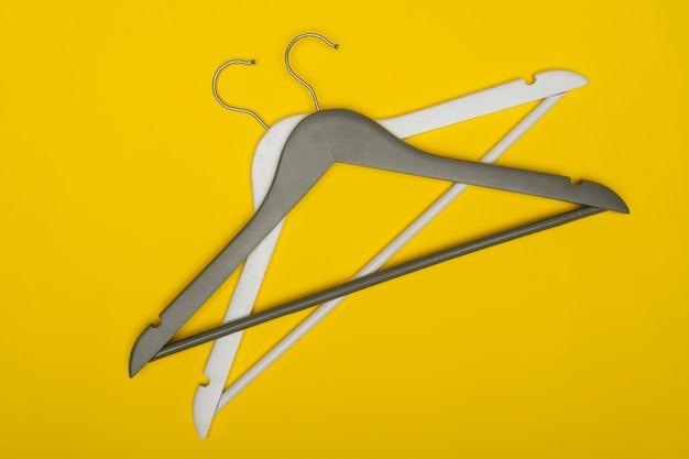 Cintres en bois blanc et gris sur fond jaune, vue du dessus. concept de garde-robe.
