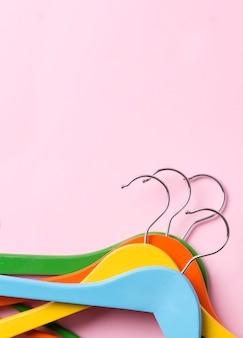 Cintres en bois multicolores à plat créatifs à table pastel rose avec style minimaliste de l'espace de copie.