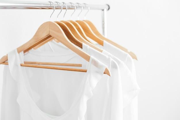 Cintres en bois avec des vêtements blancs pour femmes d'été