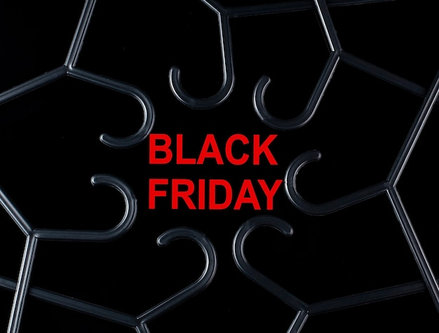 Cintres noirs et texte black friday sur fond noir. réductions. vente saisonnière.