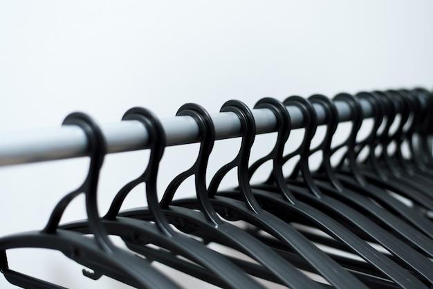 Des cintres en plastique noir pendent. de nombreux cintres différents.