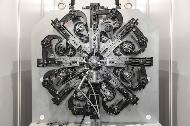 Cintreuse de fil automatique, centre d'usinage cnc de haute précision fonctionnant, opérateur faisant le processus de pièce de ressort automobile en usine.