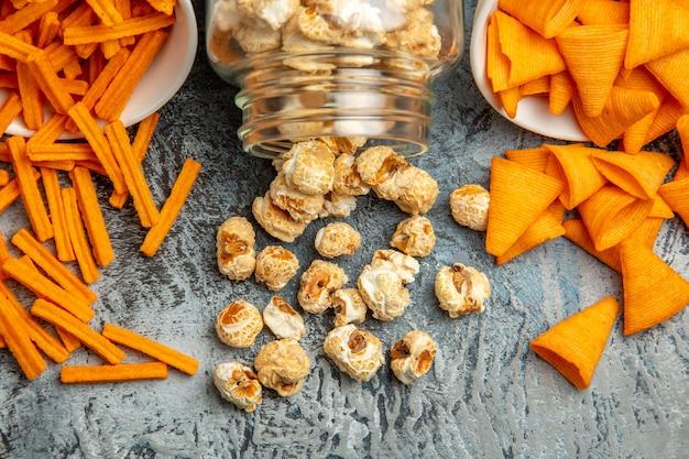 Cips de fromage vue de face avec pop-corn sur fond clair