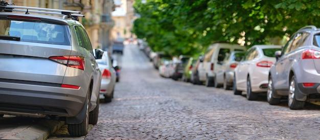 Circulation urbaine avec des voitures garées en file côté rue.