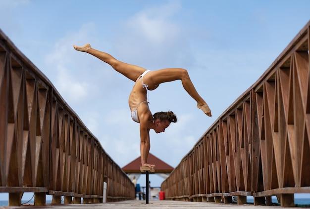Cirque féminin flexible faisant le poirier à l'envers sur la jetée