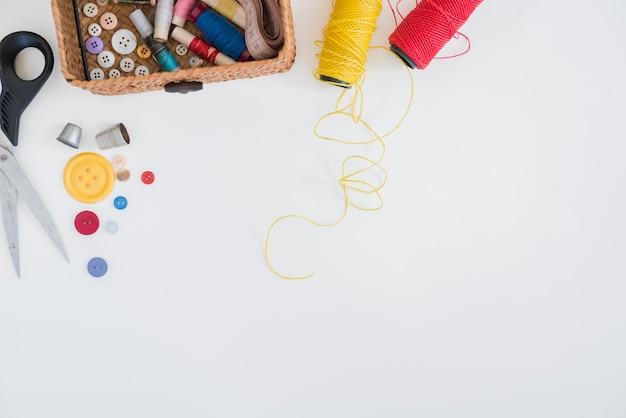 Ciseaux; boutons; dé; fil rouge et jaune isolé sur fond blanc