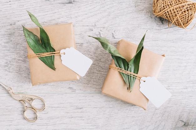 Ciseaux et cadeaux emballés avec étiquette et feuilles sur fond en bois