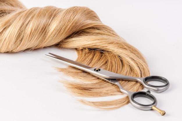 Ciseaux de coiffeur avec mèche de cheveux blonds sur fond blanc