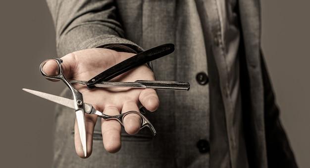 Ciseaux de coiffeur et rasoir droit, salon de coiffure. l'homme en costume tient dans sa main un rasoir vintage et des ciseaux. homme en salon de coiffure.