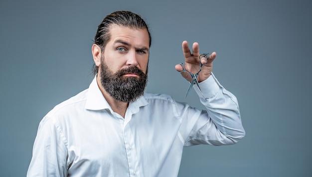Ciseaux de coiffeur. salon de coiffure vintage, rasage. homme en salon de coiffure, coupe de cheveux, rasage. homme barbu isolé sur fond gris. coupe de cheveux de l'homme au salon de coiffure. ciseaux de coiffeur, salon de coiffure.
