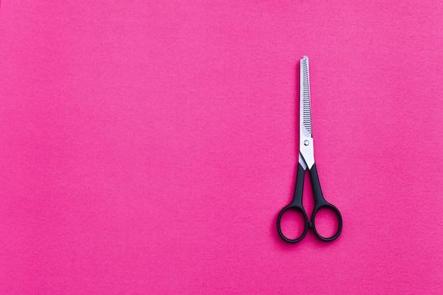 Ciseaux de coiffure professionnels sur fond rose