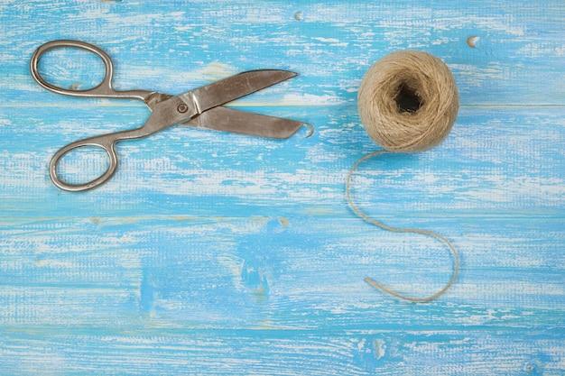 Ciseaux et une corde rugueuse sur une table rustique bleue.