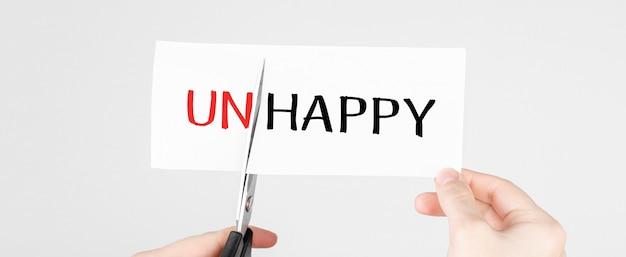 Ciseaux coupant du papier blanc avec le texte malheureux, changez le mot en heureux.