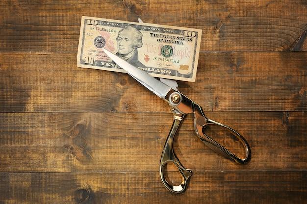 Ciseaux coupe billet de dollar sur fond de bois