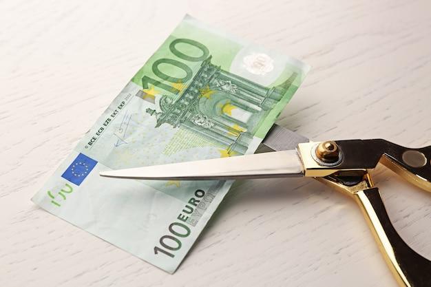 Ciseaux coupe les billets en euros sur la table